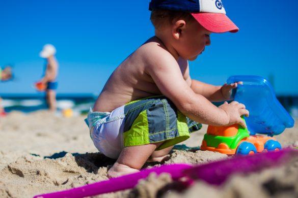 enfant qui joue dans le sable avec jouets