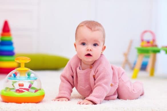 Petite fille bébé joue avec une toupie d'eveil