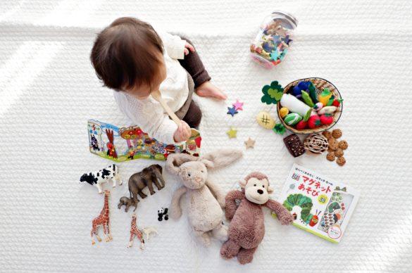 enfant assis avec des jouets autour de lui
