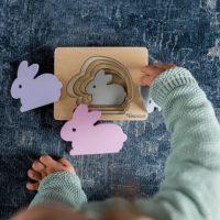 jeune enfant joue avec un puzzle en bois