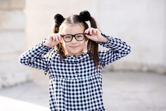 fille porte une robe à carreaux et des lunettes