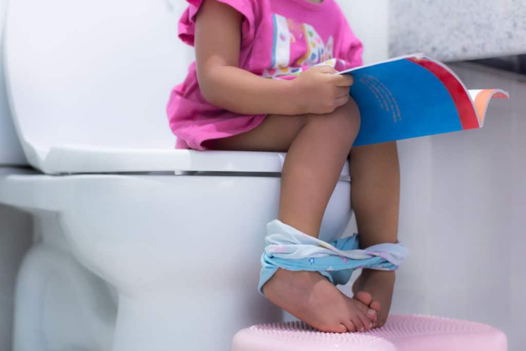 petite fille assise sur les toillettes