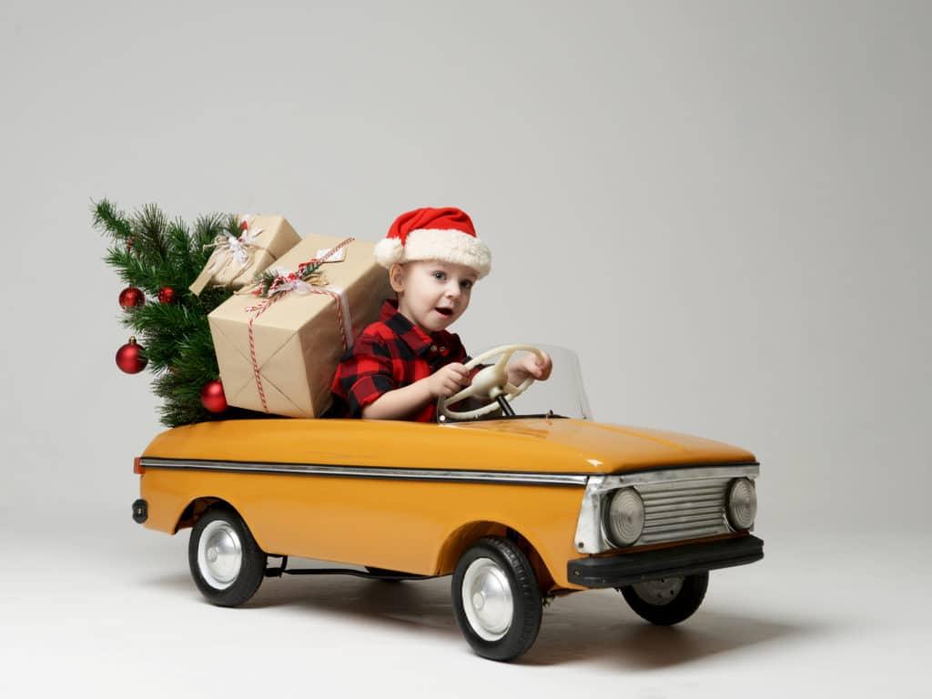 enfant conduit une petite voiture avec cadeaux noel