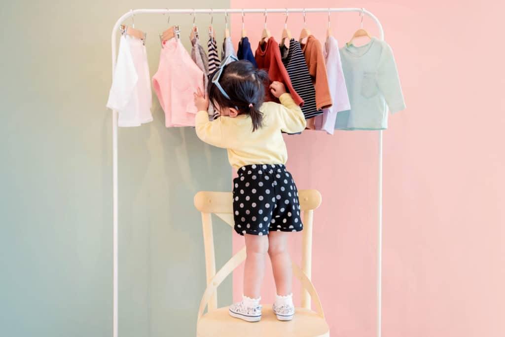 une petite fille choisis des vêtements