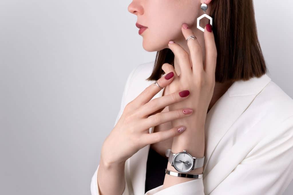 femme porte une montre et boucles d'oreilles
