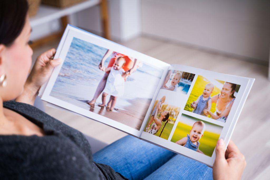 une femme regarde un album photo personnalisé