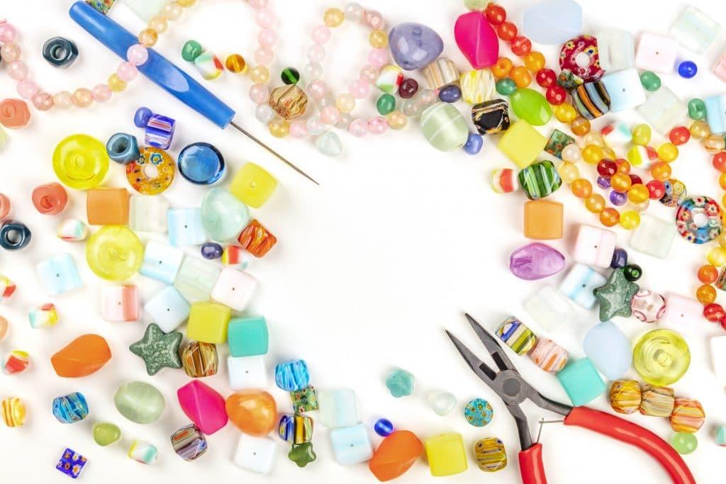 perles de couleurs posées sur une table blanche