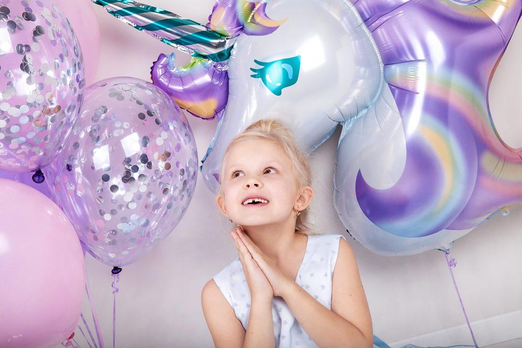 Petite fille blonde entourée de ballon paillettes et licorne