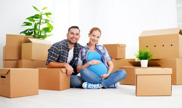 femme enceinte et homme assis à côté de cartons de déménagement