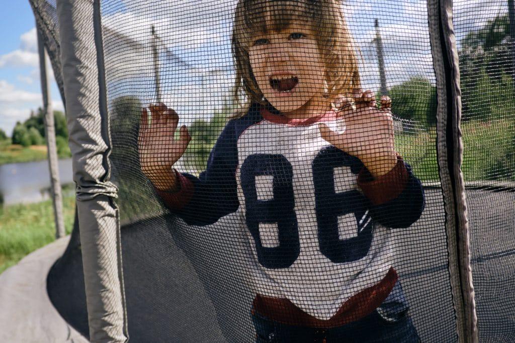 enfant derrière un filet de trampoline